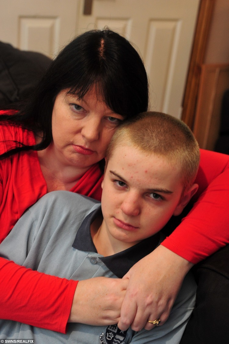 Joshua Star-Harris, a Year 8 pupil at St Mary's College in Hull, East Yorkshire, dyed his hair blue and shaved it off to raise money for Cancer Research. Joshua is pictured at home with his mother Ellie Star. See Ross Parry copy RPYHAIR : A teenager has been plucked from his classroom after he dyed his hair an exotic shade of blue - for CHARITY. Joshua Star-Harris, a Year 8 pupil at a school in Hull, East Yorks., dyed his hair blue before shaving it off to raise cash for Cancer Research UK and the homeless. After returning to St Mary's College from the Christmas break, 13-year-old Joshua was told he would not be allowed into normal lessons because some dye still remained in his hair - and was sent to the pastoral centre - a segregation area of the school for naughty pupils. His anxious mum Ellie Star says she asked the school how short she could cut his hair to ensure the dye was removed.