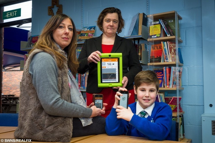 """Joe Everitt with his mum Tonie and Head teacher Caren Earp. Joe has an app which monitors his blood sugar. See SWNS story SWBLOOD; A diabetic schoolboy is one of the first in the UK to get a gadget which allows his mum to remotely check his blood via her phone - and TEXTS her when he needs a sugar hit. Joseph Everitt, nine, developed type 1 diabetes """"out of the blue"""" a year and a half ago and regularly has to monitor his blood to maintain his sugar levels. His parents had to prick his fingers up to TEN times a day, leaving them with sleepless nights and Joseph with numb fingers. They researched online and discovered a new gadget which constantly monitors his glucose levels through a sensor on his tummy."""