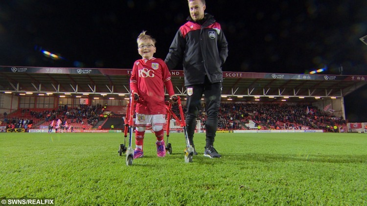 This is the heartwarming moment a young cerebral palsy sufferer took his first steps in front of 15,000 football fans - who helped fund a £50,000 operation to enable him to walk.  See SWNS story SWSTEPS:  Oskar Pycroft, seven, united fans from two rival clubs in his home city of Bristol with an appeal to pay for the procedure to strengthen muscles in his legs. Fans from Bristol City and Bristol Rovers put aside their differences to raise £57,000 in a variety of charity events. After undergoing surgery at Bristol Children's Hospital he vowed to walk onto the pitch at his beloved City's ground when he had recovered enough strength.