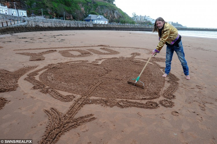 Geoffrey Ward creates a special message for Lee Piddington and Kirsty Bailey on Torre Abbey Sands, Torquay. See SWNS story SWSAND; A bride-to-be was stunned after her fiance proposed with a giant artistic message - written in the SAND. Romantic Lee Piddington, 28, organised for the message to be written on beach for girlfriend Kirsty Bailey, 29, on Christmas Eve. He enlisted the help of the renowned artist known as the Sandman, whose real name is Geoffrey Ward, who skilfully carved 'Will you be my wife?' in a special surprise message. On the day, a nervous Lee suggested a walk along the seafront in Torquay, Devon, so that Kirsty would see the message.