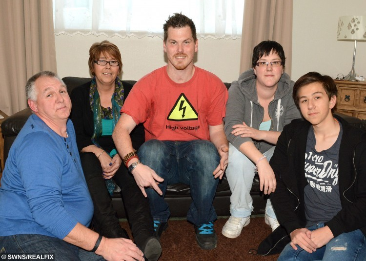 Ash Coe (centre) who survived a 33,000 volt electric shock. Also pictured are his family Paul Winter - Step dad, Debbie Geall - mum, Emma Coe - sister and Adam Geall-Winter - brother. See SWNS story SWSHOCK; A man suffered three heart attacks and had his heart stop for 35 minutes after suffering a 33,000-volt electric shock which should have killed him. Ash Coe, 31, who lives in Forches with his mum Debbie Geall and stepdad Paul Winterall corr, was working at Knockworthy Farm in Huntshaw when the accident happened in March 2013. He has very little recollection of the accident, and lost six years' memory leaving him thinking he was 23 when he woke up. Ash was unconscious for 13 days and spent a total of four months at Royal Devon and Exeter Hospital before having to learn to walk and talk again.