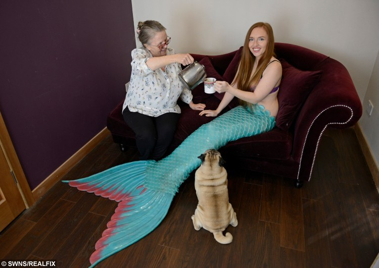 Professional mermaid Melanie Long, 25, from Old Kilpatrick, sharing a cup of tea with her mum and dog Pablo. See Centre Press copy CPMERMAID: A girl who grew up idolising Ariel the Disney sea princess has achieved her dream - and now makes her living as a real life mermaid. Flame-haired Melanie Long, 25, grew up surrounded by murals of Ariel in her bedroom and told anyone who would ask that she wanted to be The Little Mermaid. But unlike most childhood dreams and ambitions, hers has come resoundingly true after she moved to Phuket, Thailand, five years ago to travel and work as a diver. Initially, Melanie, from Clydebank, West Dunbartonshire, worked as a scuba diving instructor.