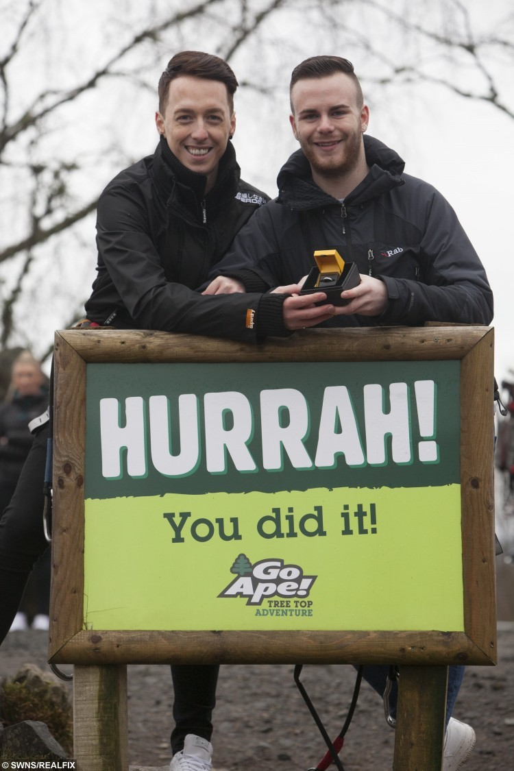 "Zac Louden (R) Colin Nicholson (L) at Go Ape Aberfoyle in Queen Elizabeth Forest Park. See Centre Press story CPHAPPY; Stunned Colin Nicholson got the surprise of his life as he zoomed down a 150ft high zip wire – his partner Zac was waiting at the bottom with a ""Will you marry me?"" Sign. After a whirlwind romance, Zac Louden, 20, was looking for an adventurous way to propose to Colin, 31. So he decided to return to the location of their first date – Go Ape in Aberfoyle, Stirlingshire – and pop the question."