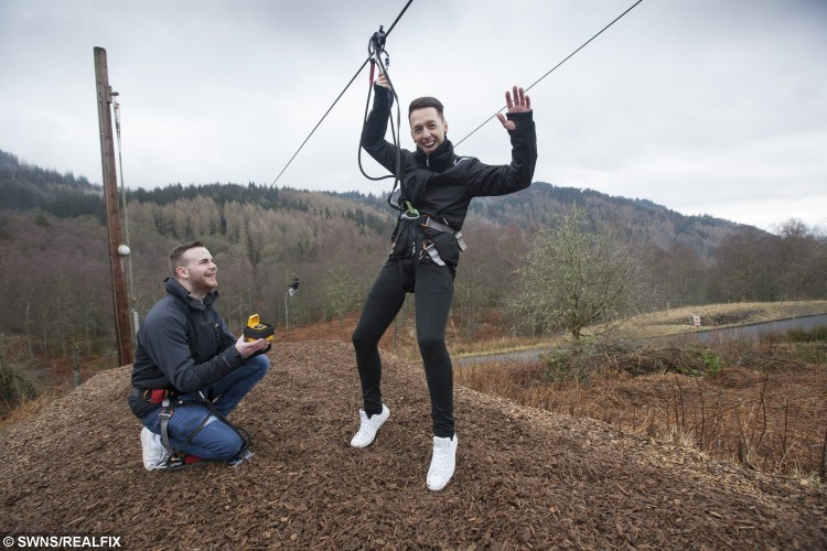 "Zac Louden (L) Colin Nicholson (R) at Go Ape Aberfoyle in Queen Elizabeth Forest Park. See Centre Press story CPHAPPY; Stunned Colin Nicholson got the surprise of his life as he zoomed down a 150ft high zip wire – his partner Zac was waiting at the bottom with a ""Will you marry me?"" Sign. After a whirlwind romance, Zac Louden, 20, was looking for an adventurous way to propose to Colin, 31. So he decided to return to the location of their first date – Go Ape in Aberfoyle, Stirlingshire – and pop the question."