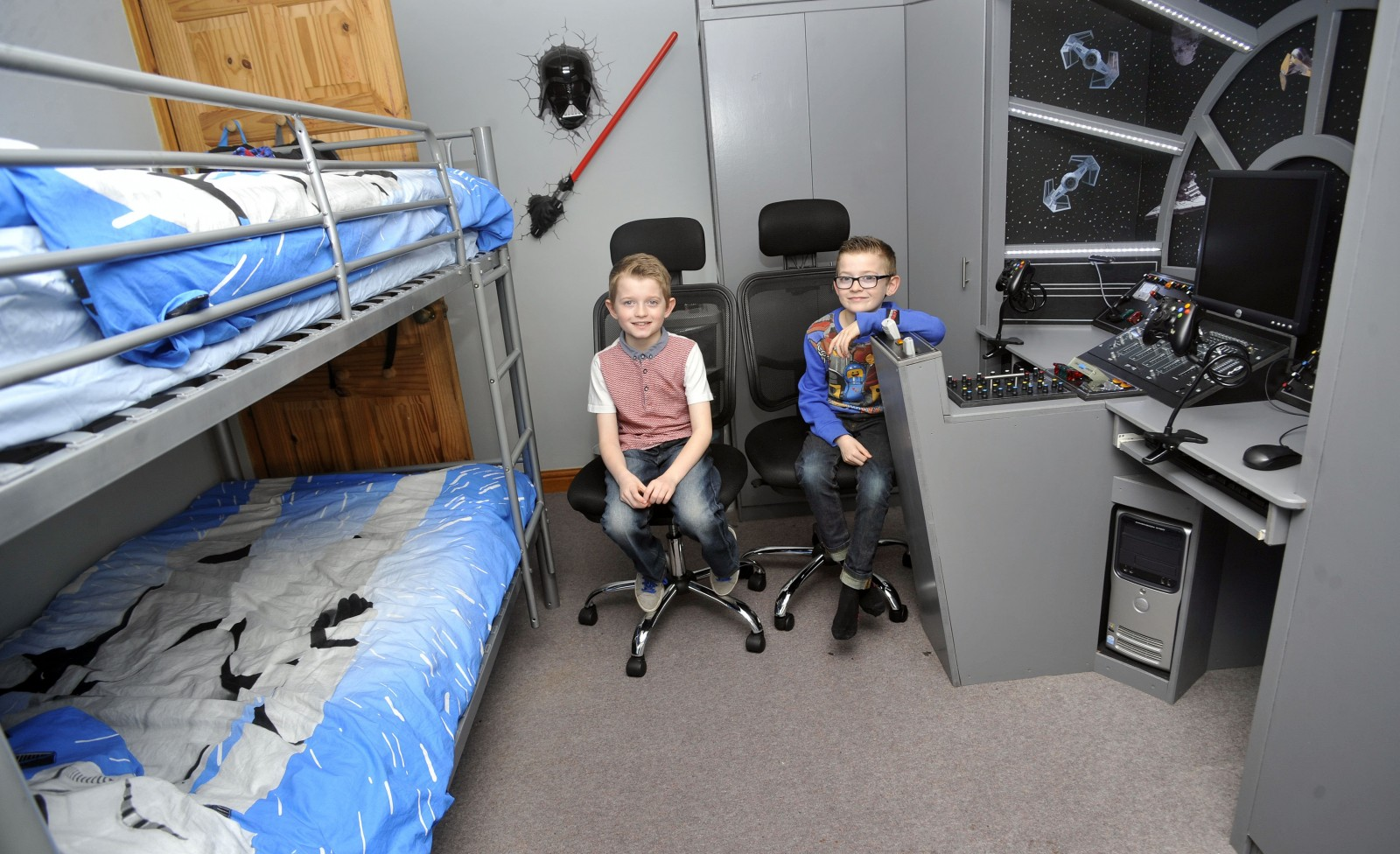 (L-R) Dylan and George in their Millennium Falcon bedroom in Thornton-Cleveleys, Lancs., See Ross Parry Copy RPYSTAR : A devoted dad gave his kids a present that was out of this world - by transforming their room into a life-size replica of a Star Wars SPACESHIP. David Bonney, 47, surprised his Star Wars superfan kids, Dylan, nine, and George, eight, with a new bedroom based on the iconic Millennium Falcon from the hit movie franchise. The father-of-five hid his efforts for a month from his two sons who had no idea their sci-fi fantasies were about to come to life. 9 March 2016.