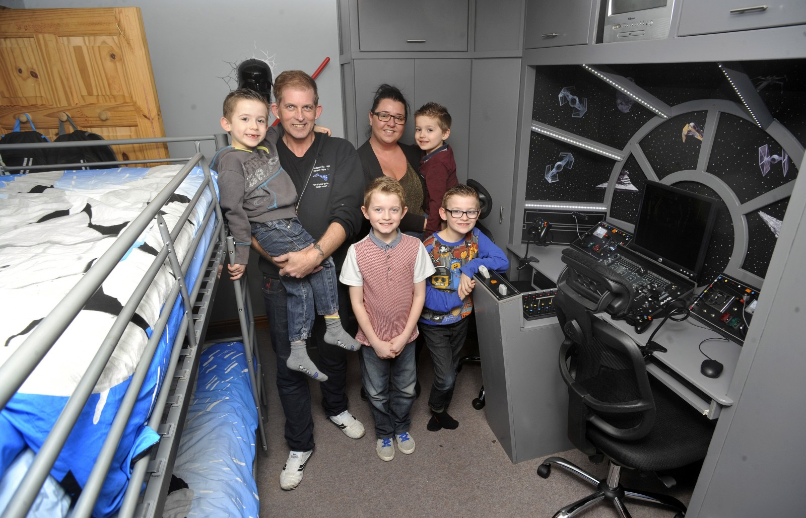 (L-R)Spencer, dad David, Dylan, mum Emma with Taylor and George in the Millennium Falcon bedroom in Thornton-Cleveleys, Lancs., See Ross Parry Copy RPYSTAR : A devoted dad gave his kids a present that was out of this world - by transforming their room into a life-size replica of a Star Wars SPACESHIP. David Bonney, 47, surprised his Star Wars superfan kids, Dylan, nine, and George, eight, with a new bedroom based on the iconic Millennium Falcon from the hit movie franchise. The father-of-five hid his efforts for a month from his two sons who had no idea their sci-fi fantasies were about to come to life. 9 March 2016.