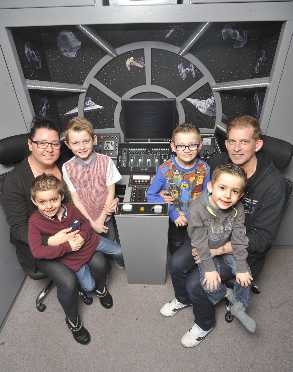 (L-R) Taylor with mum Emma, Dylan, George, Spencer with dad David in the Millennium Falcon bedroom in Thornton-Cleveleys, Lancs., See Ross Parry Copy RPYSTAR : A devoted dad gave his kids a present that was out of this world - by transforming their room into a life-size replica of a Star Wars SPACESHIP. David Bonney, 47, surprised his Star Wars superfan kids, Dylan, nine, and George, eight, with a new bedroom based on the iconic Millennium Falcon from the hit movie franchise. The father-of-five hid his efforts for a month from his two sons who had no idea their sci-fi fantasies were about to come to life. 9 March 2016.