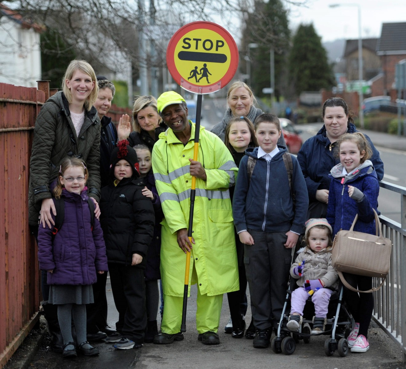 """FILE PICTURE - Local parents and children show their support for local lollipop man Nkosana Mdikane, 73, from Dumbarton, Dunbartonshire, Scotland, outside Aitkenbar Primary School in Dumbarton, February 27, 2015, where he has been told to stop high fiving the school children. See Centre Press story CPLOLLIPOP; A cheery lollipop man was forced to resign with a """"bleeding heart"""" after council bosses BANNED him from dancing and high-fiving school children. Nkosana Mdikane, 75, was hailed 'Scotland's happiest lollipop man' after helping thousands of kids cross the road with his friendly greetings. He was praised for his """"excellent service"""" when he took up the road safety job outside Aitkenbar Primary in Dumbarton with West Dunbartonshire Council in 2013. But grumpy officials performed a U-turn and told him lollipop men must """"remain static with one hand on their stick and the other stretched outwards""""."""