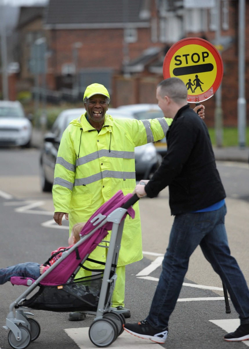 """FILE PICTURE - Lollipop man Nkosana Mdikane, 73, from Dumbarton, Dunbartonshire, Scotland, outside Aitkenbar Primary School in Dumbarton, February 27, 2015, where he has been told to stop high fiving the school children. See Centre Press story CPLOLLIPOP; A cheery lollipop man was forced to resign with a """"bleeding heart"""" after council bosses BANNED him from dancing and high-fiving school children. Nkosana Mdikane, 75, was hailed 'Scotland's happiest lollipop man' after helping thousands of kids cross the road with his friendly greetings. He was praised for his """"excellent service"""" when he took up the road safety job outside Aitkenbar Primary in Dumbarton with West Dunbartonshire Council in 2013. But grumpy officials performed a U-turn and told him lollipop men must """"remain static with one hand on their stick and the other stretched outwards""""."""