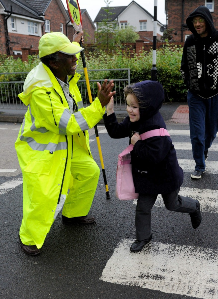 """FILE PICTURE - Dancing Lollipop man Nkosana Mdikane with a daily song and dance and his huge smile outside Aitkenbar Primary School in Dumbarton, West Dunbartonshire, he is Scotland's happiest lollipop man. See Centre Press story CPLOLLIPOP; A cheery lollipop man was forced to resign with a """"bleeding heart"""" after council bosses BANNED him from dancing and high-fiving school children. Nkosana Mdikane, 75, was hailed 'Scotland's happiest lollipop man' after helping thousands of kids cross the road with his friendly greetings. He was praised for his """"excellent service"""" when he took up the road safety job outside Aitkenbar Primary in Dumbarton with West Dunbartonshire Council in 2013. But grumpy officials performed a U-turn and told him lollipop men must """"remain static with one hand on their stick and the other stretched outwards""""."""
