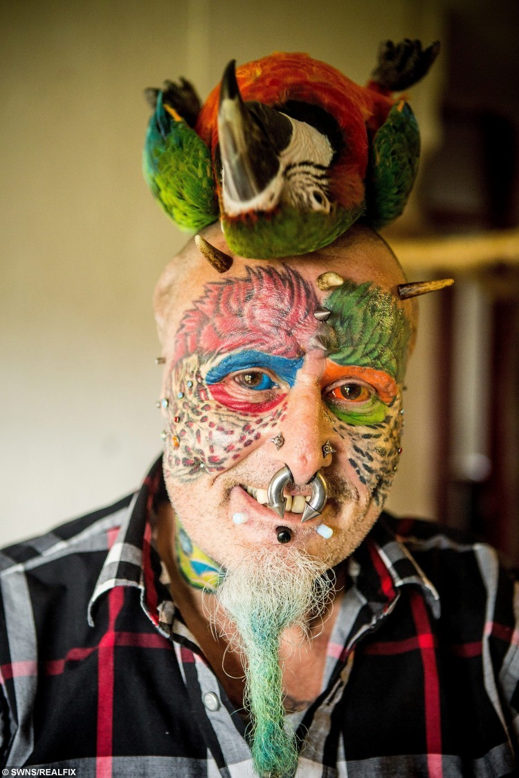 Ted Richards, 56, from Hartcliffe in Bristol, who has changed his name to Mr Parrotman.  A man who has spent years undergoing plastic surgery trying to look like his PARROTS has gone a step further and changed his name - to Mr Parrotman.  See SWNS story SWPARROT.  Bonkers Ted Richards 58, is obsessed by pets Ellie, Teaka, Timneh, Jake and Bubi and has his face and eyes tattooed with feathers.  The animal nut - who has 110 tattoos, 50 piercings and a split tongue - has also had both his ears removed by a surgeon so he looks even more like them.  Ted, of Bristol, has now changed his name by Deed Poll - to Ted Parrotman.