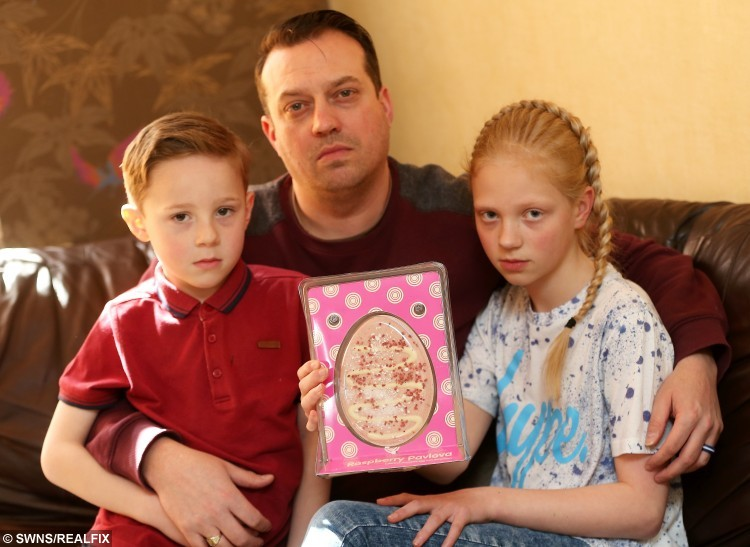 Lucy Hunt, 10 holds an Easter Egg purchased from the Range, in which she found a worm. Pictured with father Craig Hunt, 39, and brother, Ethan Hunt, 5.