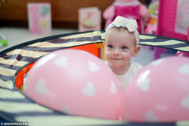 Skyla Robertson at home in Johnstone, Renfrewshire, after celebrating her 1st birthday- against the odds after being born three months early weighing just 1lb 3oz. APRIL 05 2016 See Centre Press story CPMIRACLE; A tiny baby born weighing the same as half a bag of sugar has defied the odds to reach her first birthday. Teeny tot Skyla Robertson was born 14 weeks early still inside her amniotic sac – which protects a baby as it develops in the womb. She was so small – weighing just 1lb 3oz – that doctors told her parents Nicole McGowan and Anthony Robertson there was very little chance she would survive. But a year later miracle baby Skyla is doing well, despite still having a hole in her heart and weighing half the normal weight of a youngster her age.