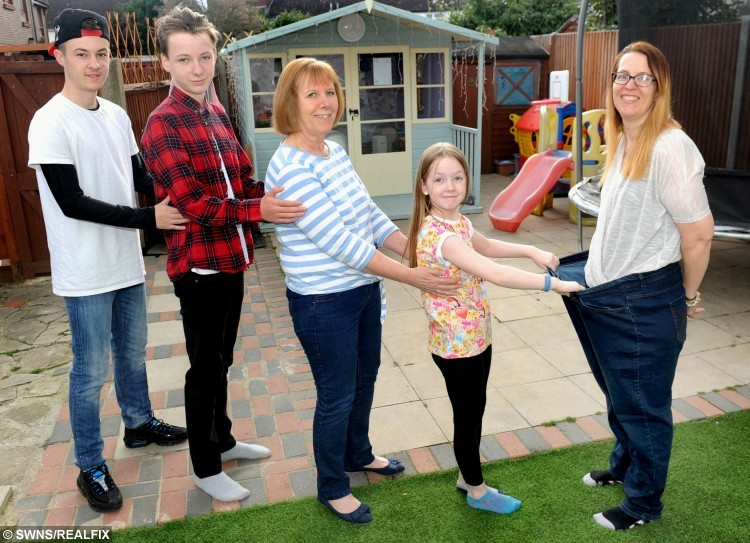 """L to R Joe Weighill 16, Connor Weighill 14, Geraldine Gellard, Dena's mum, Ciara Weighill 9 and Dena Harrison in her old trousers. Dena Harrison from Surbiton, south west London who has lost 11 stone. See SWNS story SWSLIM; A mum-of-seven says she has shed a whopping 11 stone by dropping chips - and picking up KNITTING. Dena Harrison, 42, swapped unhealthy snacks for knitting needles and lost half her body weight after fearing she was heading for a heart attack. She weighed a hefty 22 stone in February 2014 when she felt shooting pains down her left arm on a trip to the supermarket. She came up with her novel way of keeping her mind off bad foods by taking out the needles for an hour each evening to keep her hands busy. She is now 11st 8lbs - less than a stone away from her target weight of 10st 11.5lbs. Dena, a full-time carer for her husband, Darren, 48, who has learning difficulties, said: """"I can remember being in the supermarket and I could feel these pains in my arm."""