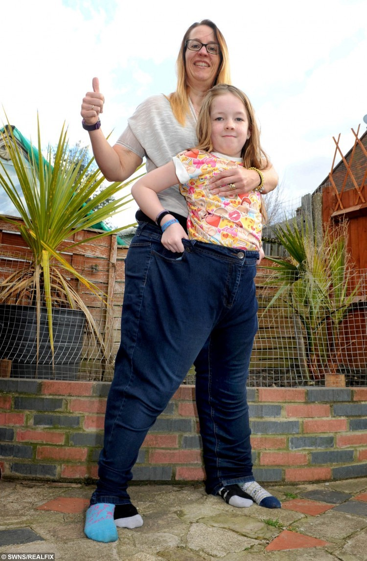 """Dena Harrison in her old trousers with her daughter Ciara Weighill. Dena Harrison from Surbiton, south west London who has lost 11 stone. See SWNS story SWSLIM; A mum-of-seven says she has shed a whopping 11 stone by dropping chips - and picking up KNITTING. Dena Harrison, 42, swapped unhealthy snacks for knitting needles and lost half her body weight after fearing she was heading for a heart attack. She weighed a hefty 22 stone in February 2014 when she felt shooting pains down her left arm on a trip to the supermarket. She came up with her novel way of keeping her mind off bad foods by taking out the needles for an hour each evening to keep her hands busy. She is now 11st 8lbs - less than a stone away from her target weight of 10st 11.5lbs. Dena, a full-time carer for her husband, Darren, 48, who has learning difficulties, said: """"I can remember being in the supermarket and I could feel these pains in my arm."""