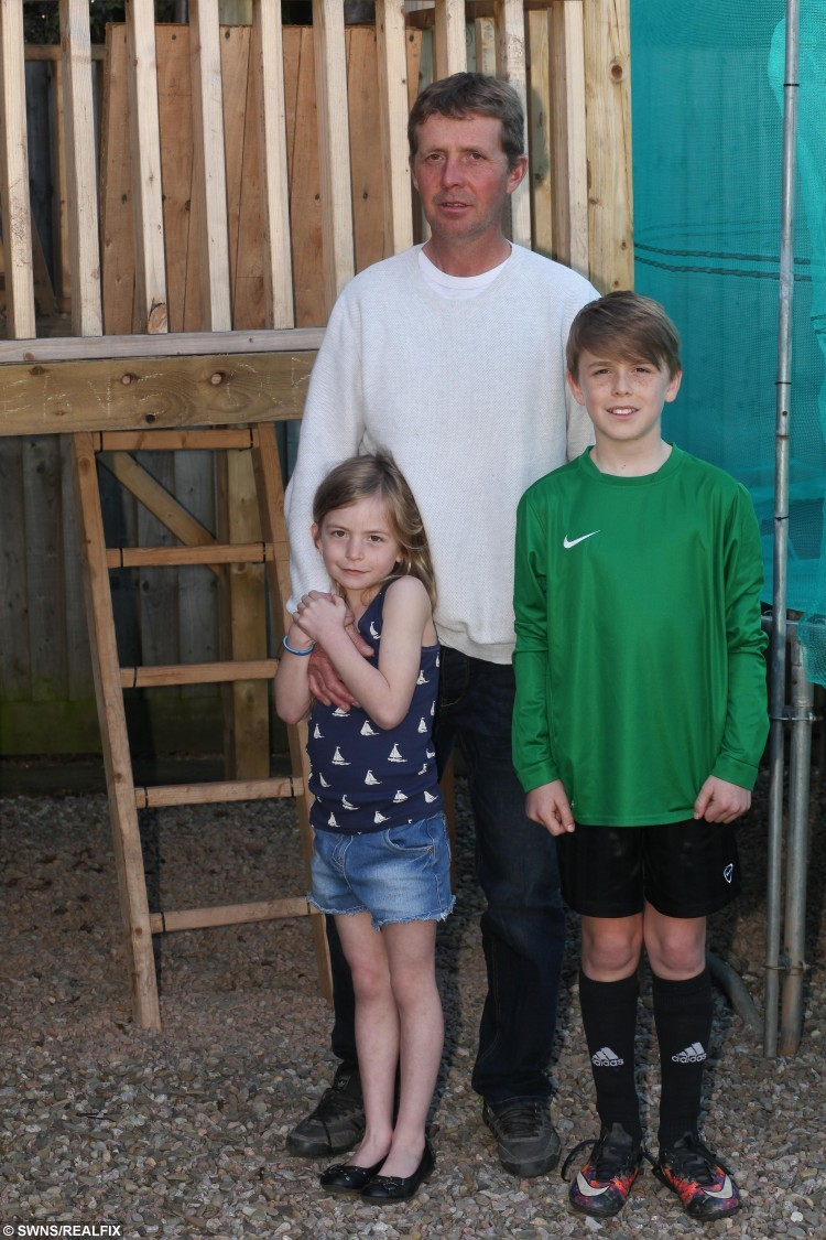 Construction worker Matt Waybourne aged 42 from Hereford, Herefordshire with his children, Lilly aged 7 and Joseph aged 12. See SWNS story SWTREE; A dad is gutted after the council told him to tear down a massive 'tree house' he built for his seven-year-old daughter - because he didn't apply for planning permission. Construction worker Mat Waybourne, 42, spent every spare evening and weekend for months building the two-storey 'shed on stilts' for daughter Lilly. He forked out £800 on the 15ft wooden house - which has a balcony, windows and two ladders - because he wanted somewhere safe for her to play during visits. But he was devastated when a council officer told him he had to tear it down because he hadn't applied for planning permission for the impressive structure.
