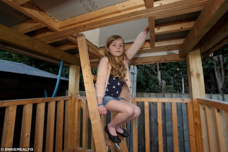 Construction worker Matt Waybourne's daughter Lilly aged 7. See SWNS story SWTREE; A dad is gutted after the council told him to tear down a massive 'tree house' he built for his seven-year-old daughter - because he didn't apply for planning permission. Construction worker Mat Waybourne, 42, spent every spare evening and weekend for months building the two-storey 'shed on stilts' for daughter Lilly. He forked out £800 on the 15ft wooden house - which has a balcony, windows and two ladders - because he wanted somewhere safe for her to play during visits. But he was devastated when a council officer told him he had to tear it down because he hadn't applied for planning permission for the impressive structure.