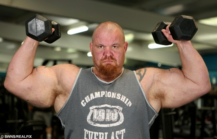 Dave Crosland, 44, flexes the UK's biggest biceps at a gym in Huddersfield.
