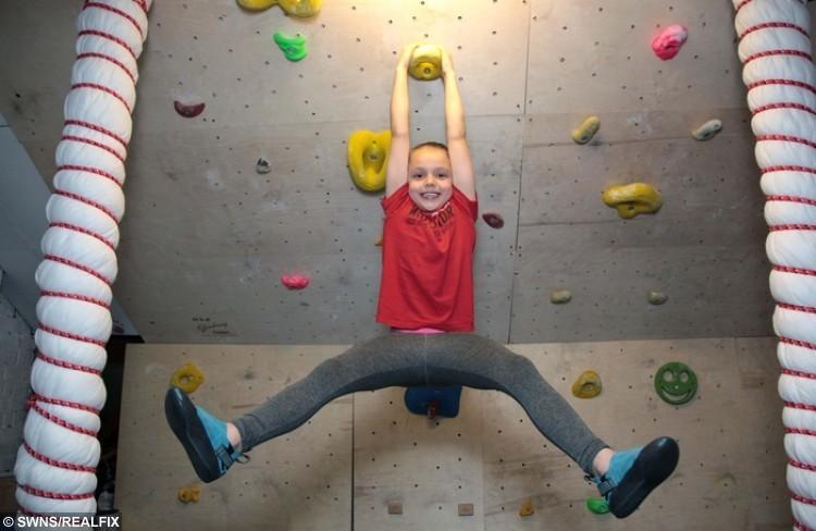 Lucy Garlick pictured on the climbing wall her parents built in their house. See National News story NNCLIMB; A nine-year-old was crowned a national climbing champion after her parents spent a small fortune converting their house - into a giant climbing frame. Lucy Garlick began climbing with her mum Natalie, 38, just three years ago and has already gone on to become a prize-winning 'Spider-girl'. Proud parents Natalie and Paul initially built a climbing wall up the staircase, after little Lucy began driving them mad by clambering over everything in the home she could. The youngster can even climb her way from the front door of their home to the bathroom without touching the floor.