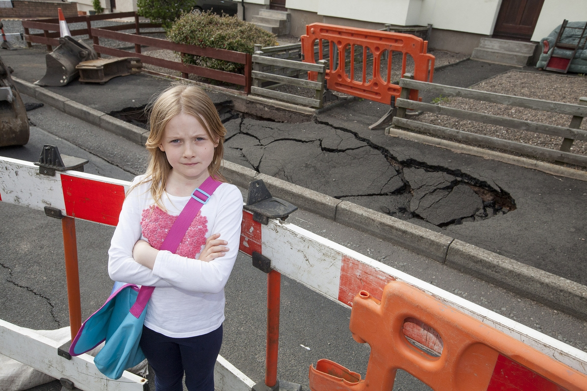 Sinkhole stops little girl from using her front door – and means she climbs neighbour's fence to get to school
