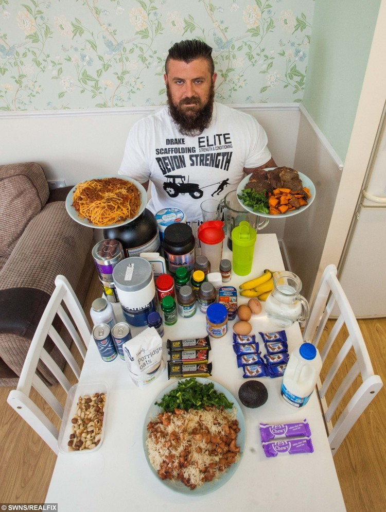 Sean Palmer from Plymouth, Devon, with his daily food intake. Sean consumes a daily diet of over 10,000 calories. See SWNS story SWSTRONG; A 24-stone strongman has revealed his 10,000 calorie-a-day diet - which includes a 2,500 calorie 'death shake' and enough steak to feed FOUR people. Sean 'The Bear' Palmer, who towers at 6ft 6ins, wolfs down gigantic meals in between his rounds as a postman - and even manages to fit in a mammoth four HOUR gym session. In a typical day, the 29-year-old shovels enough food into his mouth to feed a family, including a kilo of chicken, four portions of spag bol and three chocolate bars. He also glugs eight litres of water and a breakfast smoothie containing 2,500 calories, which makes his  daily calorie intake FOUR TIMES higher than the recommended limit.