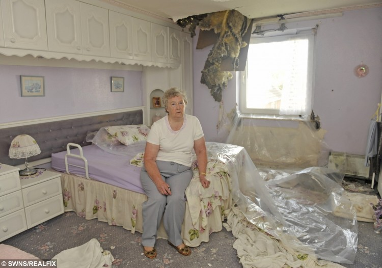 Lily Miller from Leyland, Lancs., surrounded by the damage done to her house
