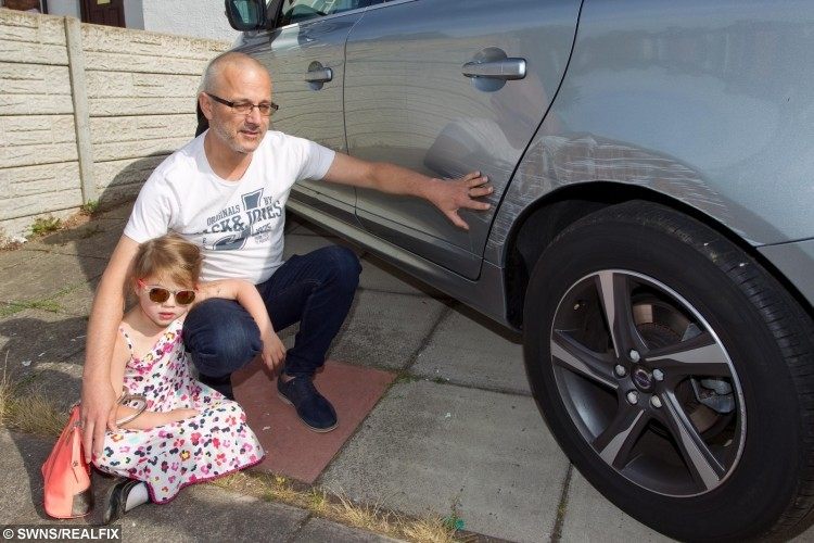 Stuart Hall with daughter Alexi (Lexi) aged 5, next to their damaged car