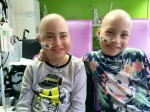 Identical twins battling a rare genetic condition are back at school a year after having stem cell transplant ops
