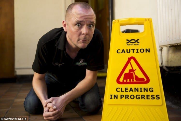 James Stevens 39, pub landlord at his property where a ghost has appeared to move and cleaning sign