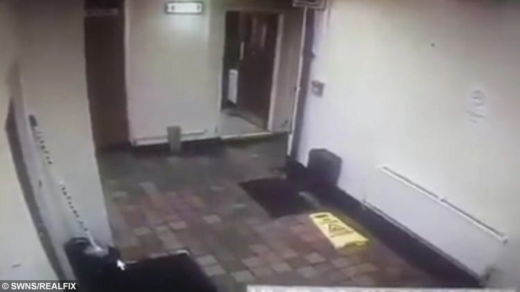 Video grab where a ghost has appeared to move a cleaning sign and mop