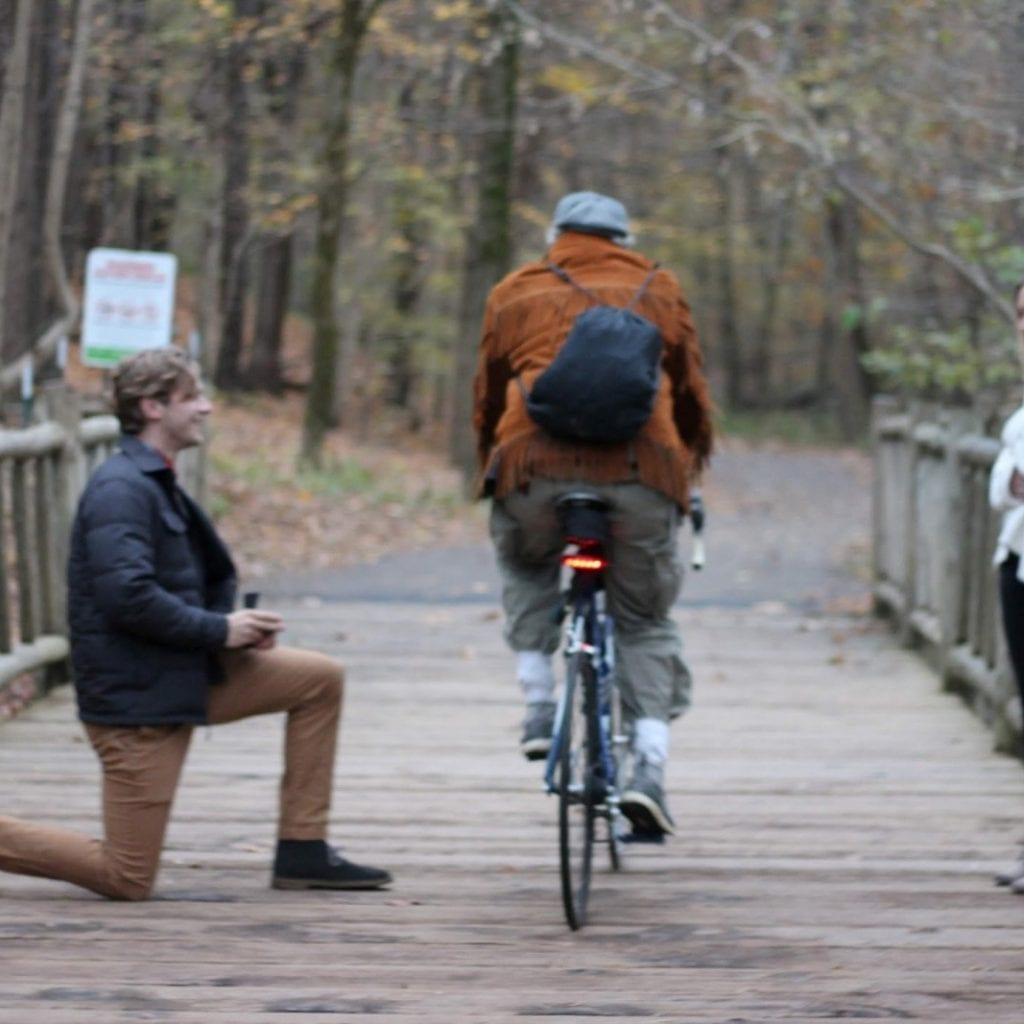 Cyclist Photobombs Couple's Intimate Bridge Proposal