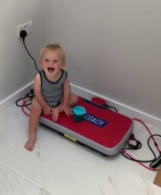 Toddler In Fits Of Giggles As He Sits On Vibrating Exercise Board